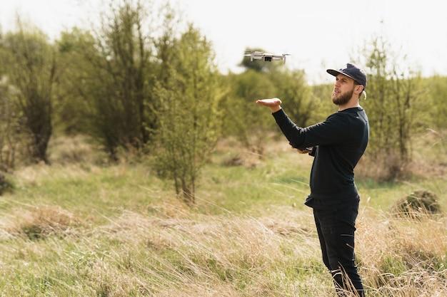 Man in volledig zwarte outfit met afstandsbediening en vliegen met een drone met veldachtergrond
