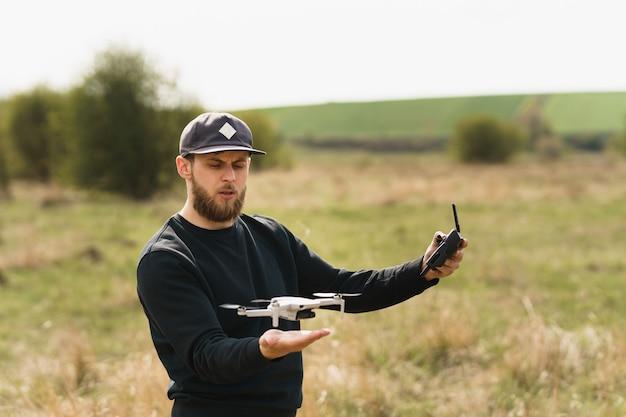 Man in volledig zwarte outfit met afstandsbediening en vliegen met een drone met veldachtergrond Premium Foto