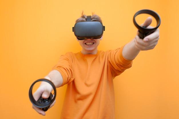 Man in vr-bril op een oranje achtergrond, een gamer houdt joysticks vast en speelt een virtuele shooter