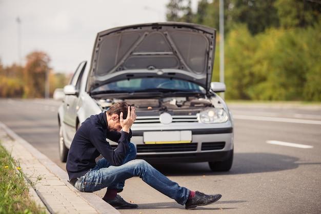 Man in wanhoop vanwege het uitvallen van zijn auto