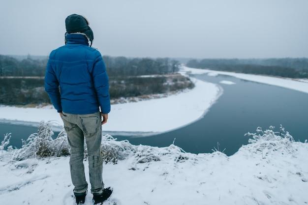 Man in warme kleren van achter staat op besneeuwde berg en kijkt naar de rivier