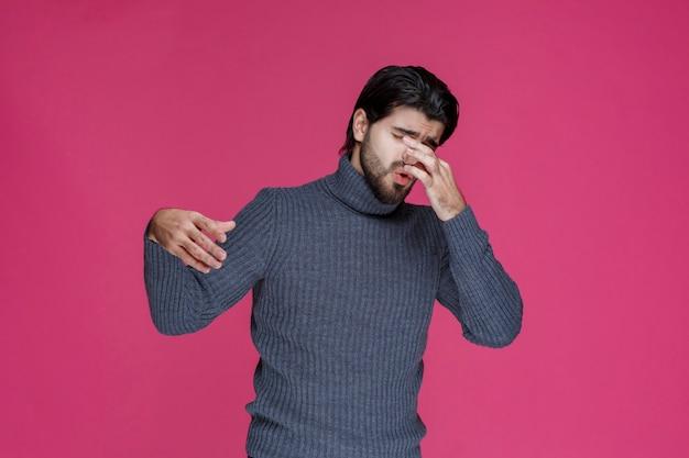 Man in warme trui ziet eruit alsof hij verkouden is en ziek wordt.