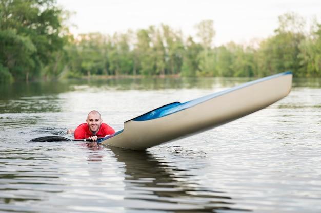 Man in water in de buurt van kajak