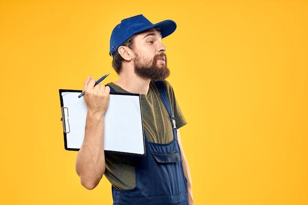 Man in werkende vorm documenten transport bezorgservice gele achtergrond. hoge kwaliteit foto