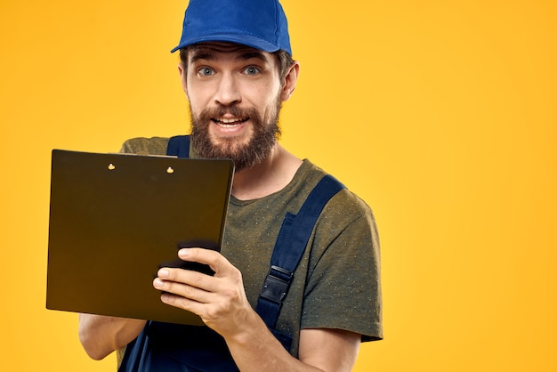 Man in werkkleding formulier documenten transport bezorgservice gele achtergrond.