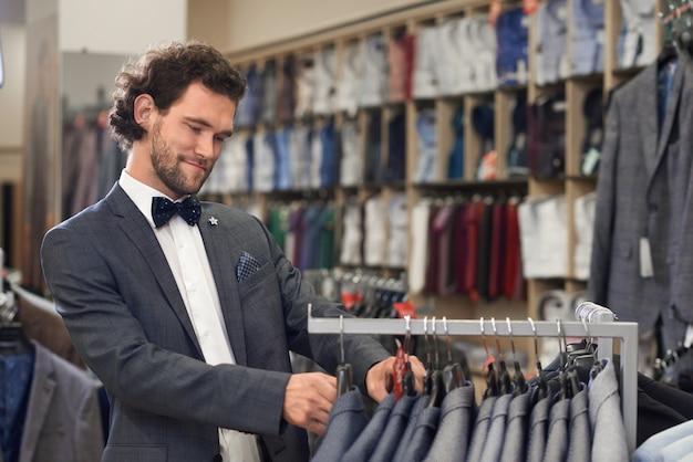 Man in winkel op zoek naar perfect bovenste deel van kostuum.