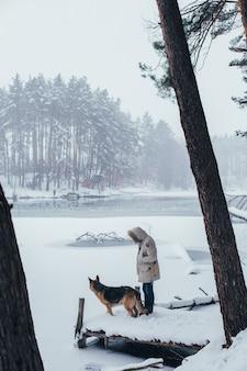 Man in winterjas in bos met herdershond