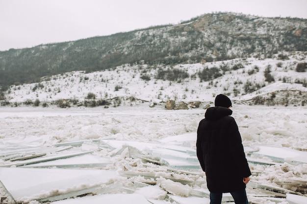 Man in winterkleren op een achtergrond van de bevroren rivier met grote ijsschotsen.
