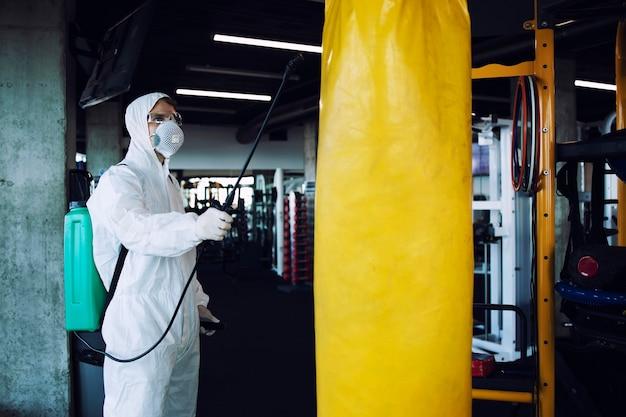 Man in wit beschermend pak desinfecteert en sproeit fitnessapparatuur om verspreiding van zeer besmettelijk coronavirus te stoppen