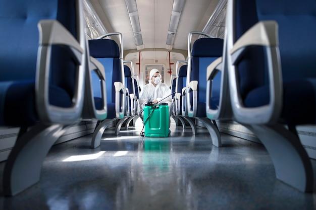 Man in wit beschermingspak desinfecteert en reinigt het interieur van de metro om de verspreiding van het zeer besmettelijke coronavirus te stoppen