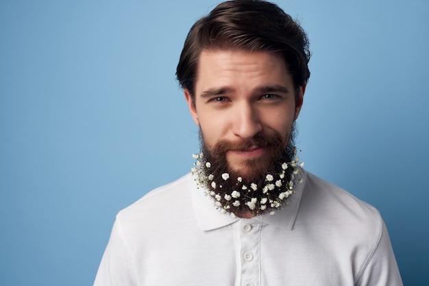 Man in wit overhemd bloemen in baard haarverzorging mode blauwe achtergrond. hoge kwaliteit foto
