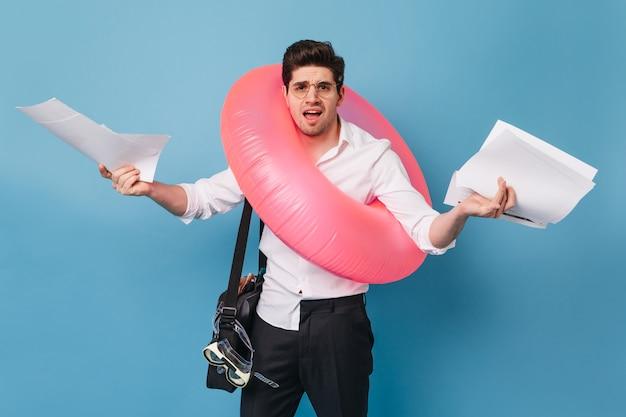 Man in wit overhemd, broek en bril gooit zijn handen in de lucht, houdt documenten vast en poseert met rubberen ring tegen blauwe ruimte.