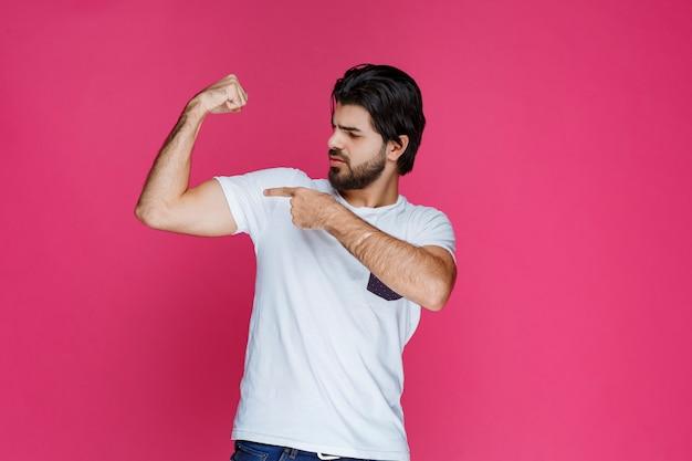 Man in wit overhemd demonstreren zijn armspieren en macht.