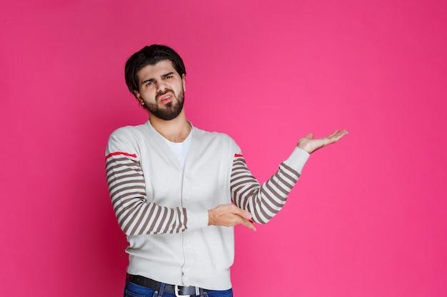 Man in wit overhemd die ergens naar wijst en iemand introduceert of gewoon de richting aangeeft.