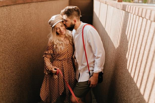 Man in wit overhemd en kaki korte broek kust zachtjes zijn positieve glimlachende blonde vrouw in bruine jurk.