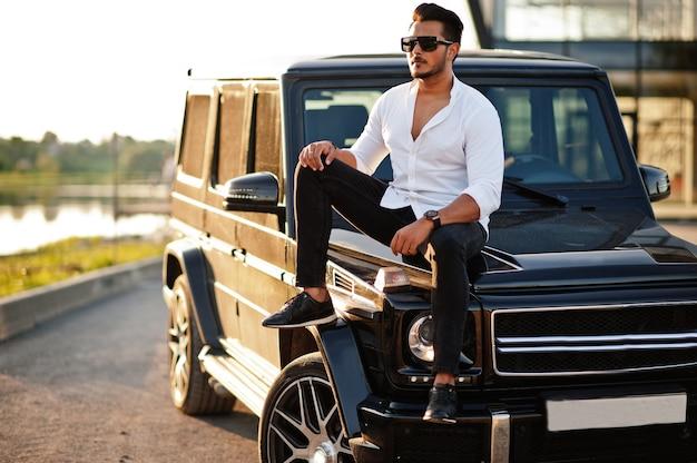 Man in wit overhemd en zonnebril poseren in de buurt van zwarte suv auto