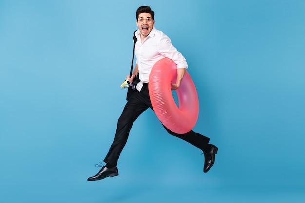 Man in wit overhemd en zwarte broek rent tegen blauwe ruimte, lacht vrolijk en houdt opblaasbare cirkel vast.
