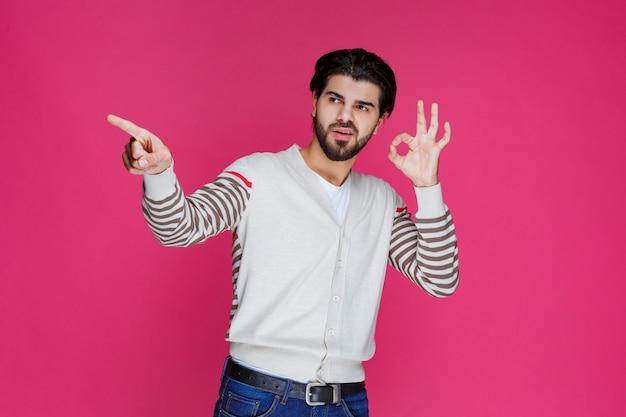 Man in wit overhemd hand cirkel ok teken maken.