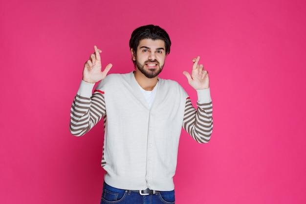 Man in wit overhemd hand dwarsteken maken.