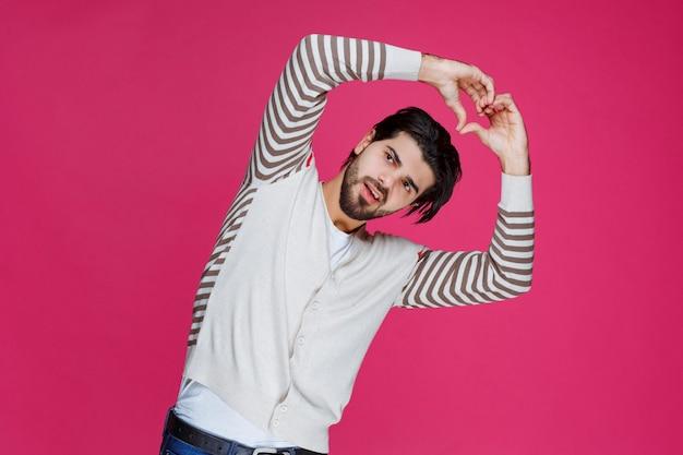 Man in wit overhemd hand hart te houden en liefde te verzenden.