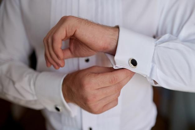 Man in wit overhemd in de buurt van manchetknopen van etalage