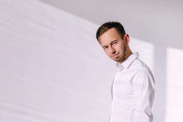 Man in wit overhemd in studio met hard zonlicht