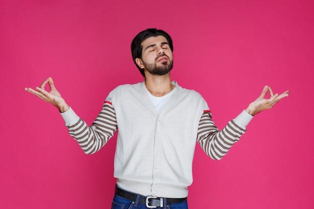 Man in wit overhemd meditatie en yoga doen. Gratis Foto