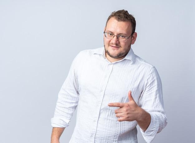 Man in wit overhemd met bril glimlachend zelfverzekerd wijzend met wijsvinger naar de zijkant staande over witte muur