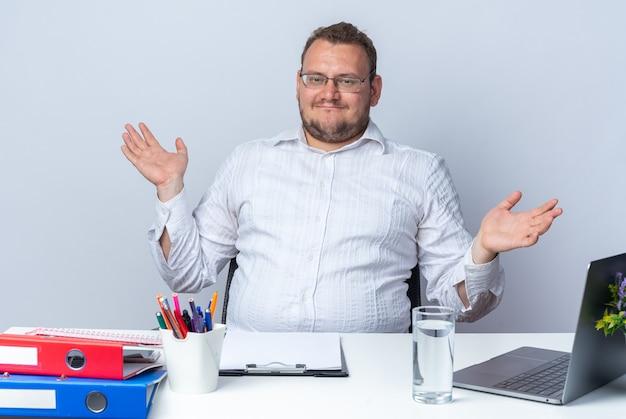 Man in wit overhemd met bril kijkend naar voorkant blij en blij spreidende armen naar de zijkanten zittend aan de tafel met laptop kantoormappen en klembord over witte muur werken op kantoor