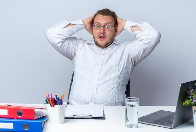 Man in wit overhemd met bril verbaasd en verrast zittend aan de tafel met laptop kantoormappen en klembord op wit