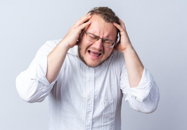 Man in wit overhemd met een bril die aan zijn haar trekt en gaat schreeuwen