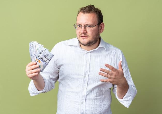 Man in wit overhemd met een bril die contant geld vasthoudt, ziet er verward en erg angstig uit