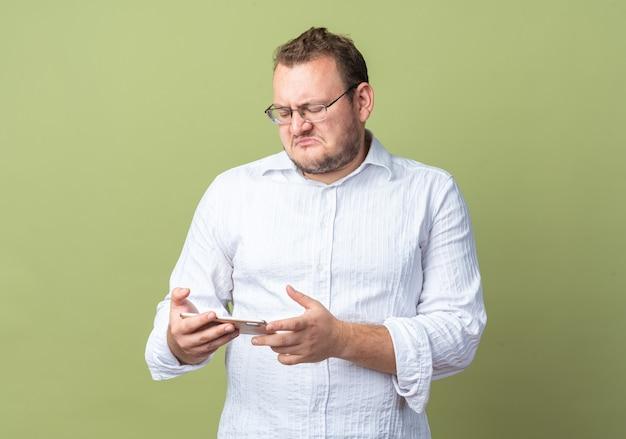 Man in wit overhemd met een bril die een smartphone vasthoudt en ernaar kijkt met een teleurgestelde uitdrukking die over een groene muur staat