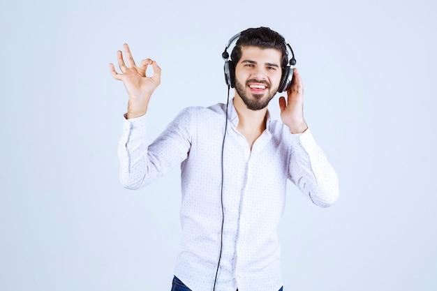 Man in wit overhemd met koptelefoon en genietend van de muziek