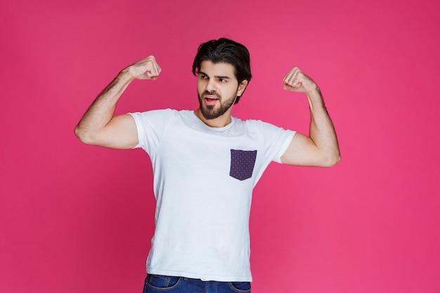 Man in wit overhemd met zijn vuist en biceps spieren.