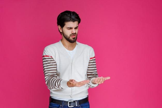 Man in wit overhemd op zoek naar iets in zijn handen.