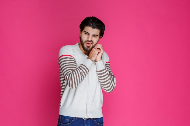 Man in wit overhemd voelt zich positief en glimlacht.