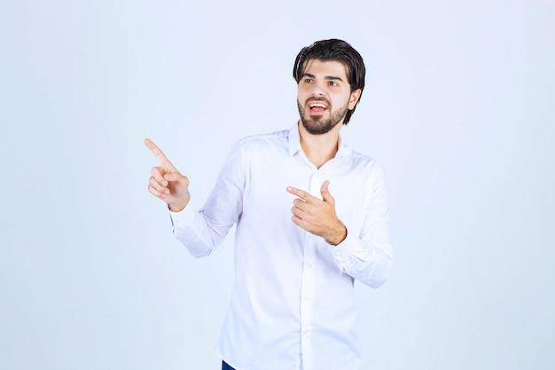 Man in wit overhemd wijzend ergens aan de linkerkant met gezichtsemoties.