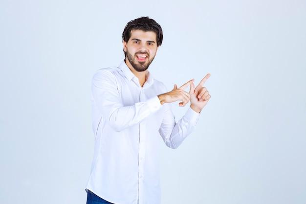 Man in wit overhemd wijzend naar iets aan de rechterkant.