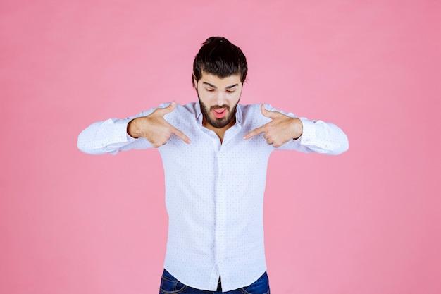 Man in wit overhemd wijzend op zichzelf.
