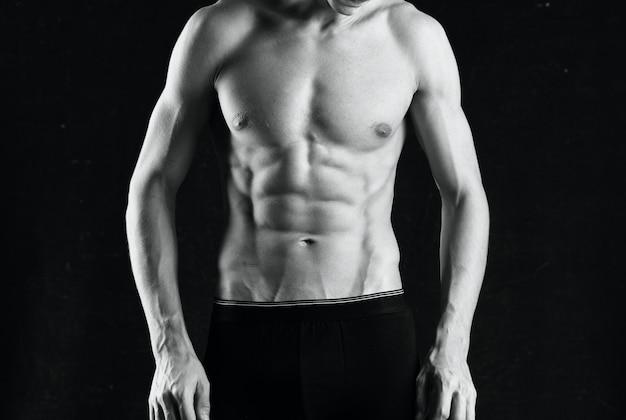 Man in wit slipje, zo'n zwarte lichaamsfitness die op een donkere achtergrond poseert