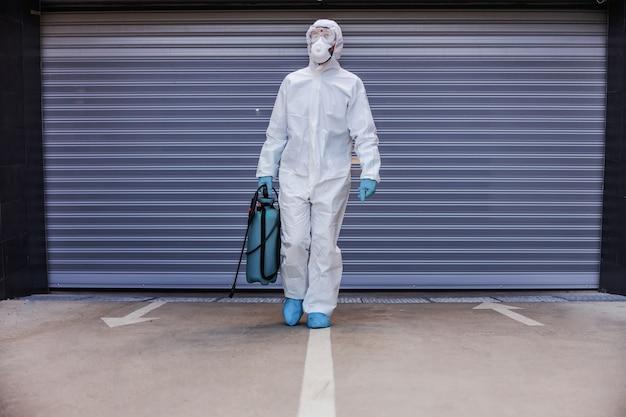 Man in wit steriel uniform met rubberen handschoenen sproeier met ontsmettingsmiddel te houden en naar camera in garage te lopen.