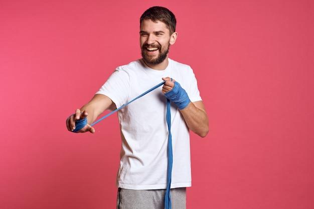 Man in wit t-shirt bindt zijn hand met een verband en model roze achtergrond
