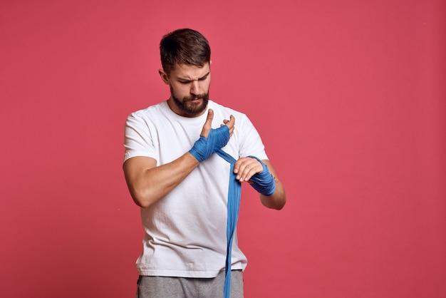 Man in wit t-shirt bindt zijn hand met een verband vechtsporten roze ruimte