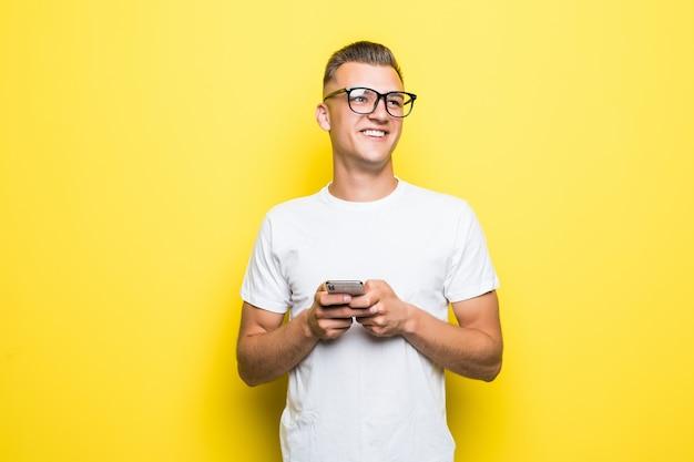 Man in wit t-shirt en bril maakt iets op zijn telefoon en neemt selfie-foto's geïsoleerd op geel