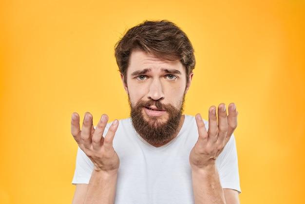 Man in wit t-shirt met handen gebaren en ontevreden op geel