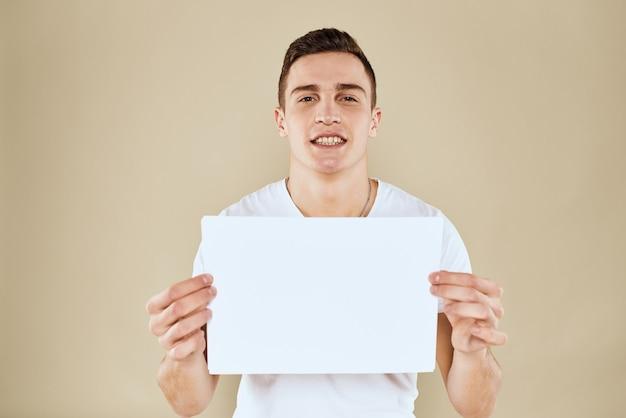 Man in wit t-shirt vel papier in handen copy space bijgesneden weergave beige