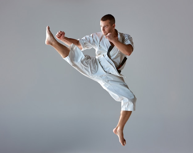 Man in witte kimono training karate