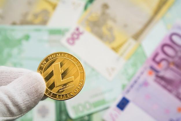 Man in witte kruidnagel met litecoin munt tussen vingers met eurobankbiljetten op de achtergrond.