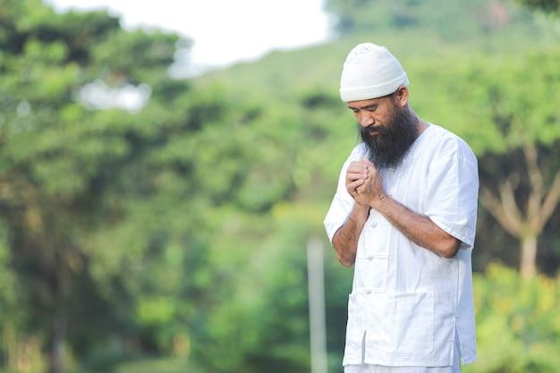 Man in witte outfit mediteren in de natuur